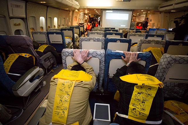 衝撃防止姿勢をとる乗客=2月18日 PHOTO: Tatsuyuki TAYAMA/Aviation Wire