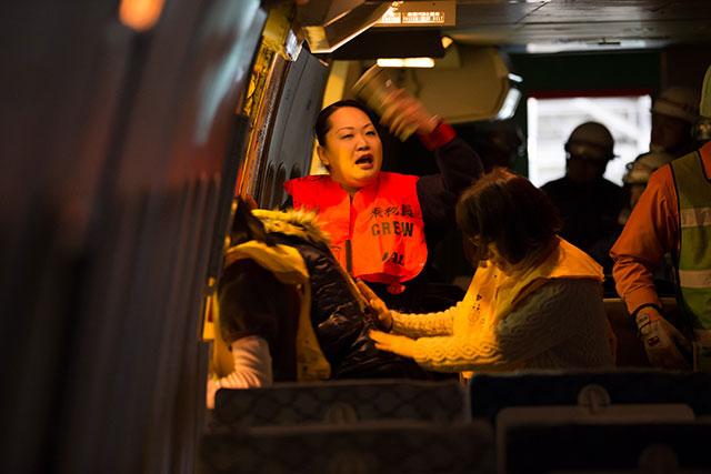乗客を機外へ誘導する客室乗務員=2月18日 PHOTO: Tatsuyuki TAYAMA/Aviation Wire
