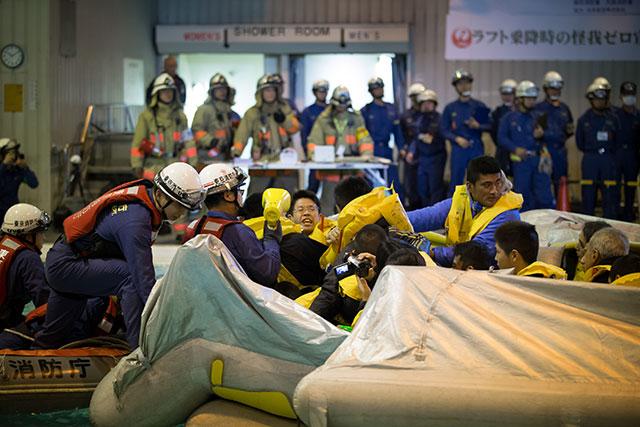 スライドラフトで脱出した乗客を救助する消防隊員=2月18日 PHOTO: Tatsuyuki TAYAMA/Aviation Wire