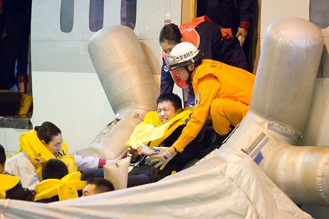 乗客を救助する客室乗務員と消防隊員=2月18日 PHOTO: Tatsuyuki TAYAMA/Aviation Wire