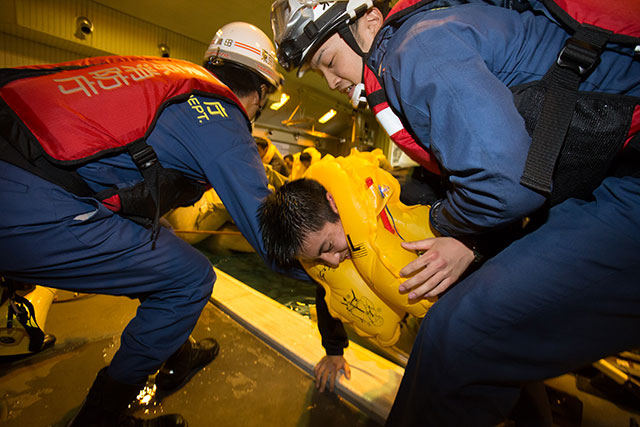 着岸したスライドラフトから乗客を抱え上げる消防隊員=2月18日 PHOTO: Tatsuyuki TAYAMA/Aviation Wire
