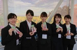 長崎空港の搭乗口でマグネットステッカーなどを手にする活水女子大学の学生(JAL提供)