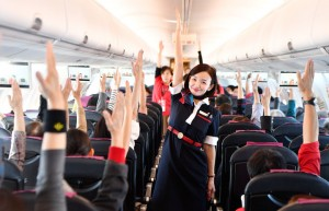 介護予防チャーターJL5745便の機内でインフライト体操を実演する客室乗務員の中村さん=18年11月3日 PHOTO: Tadayuki YOSHIKAWA/Aviation Wire