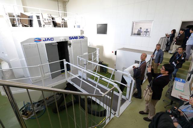 格納庫に隣接する施設でサーブ340Bのシミュレーターを見学するツアー参加者=18年12月1日 PHOTO: Masahiro SATO/Aviation Wire