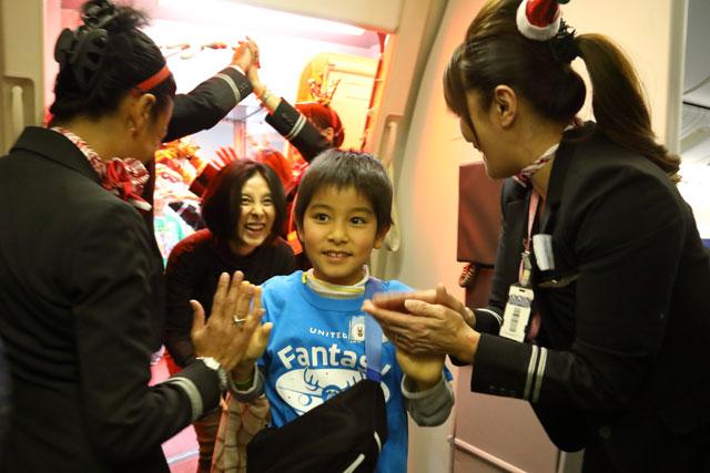 ファンタジーフライトに搭乗しユナイテッド航空の客室乗務員から歓迎を受ける親子 =19年12月11日 PHOTO: Masahiro SATO/Aviation Wire