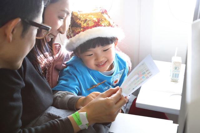 ユナイテッド航空のファンタジーフライトUA2811便の機内で空の旅を楽しむ親子=19年12月11日 PHOTO: Masahiro SATO/Aviation Wire