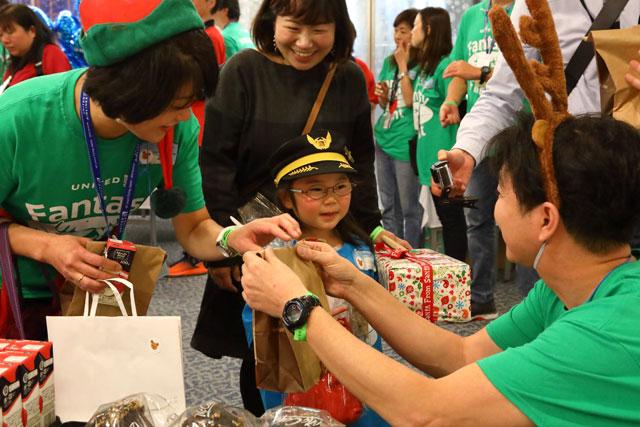 成田空港で開かれたユナイテッド航空のファンタジーフライトの到着口でスタッフからプレゼントを受け取る親子=19年12月11日 PHOTO: Masahiro SATO/Aviation Wire