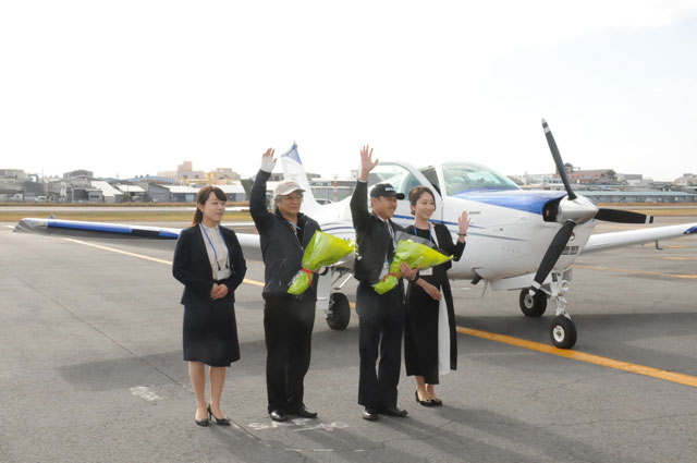 花束を贈られ関係者に手を振る植野さん(右から2人目)と渋谷さん(同3人 目)=19年12月15日 PHOTO: Yoshimasa YAMADA/Aviation Wire
