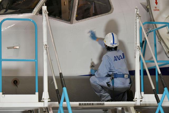 羽田空港の格納庫でANAウイングス創立10周年デカール貼付前に737-800 JA89AN を拭く整備士=20年9月23日 PHOTO: Tadayuki YOSHIKAWA/Aviation Wire